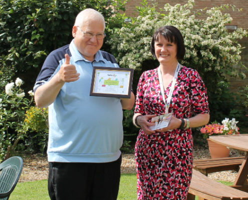 Terry Stephens receiving his award from Marie Taylor, Head of Supported and Retirement Housing at bpha