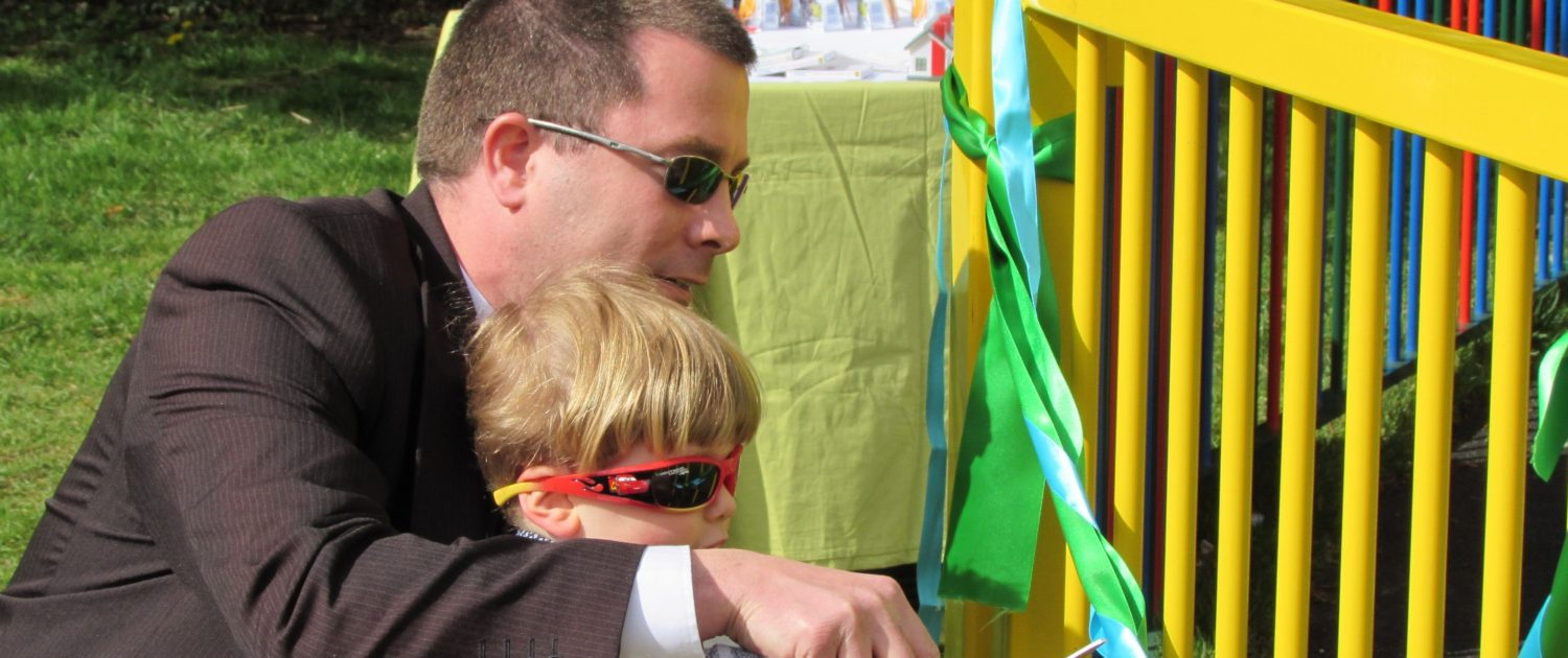 Man and son cutting a ribbon to officially open a revamped childrens playground