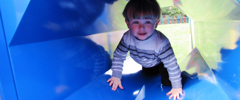 Little boy crawling through an octagonal blue tunnel in a playground