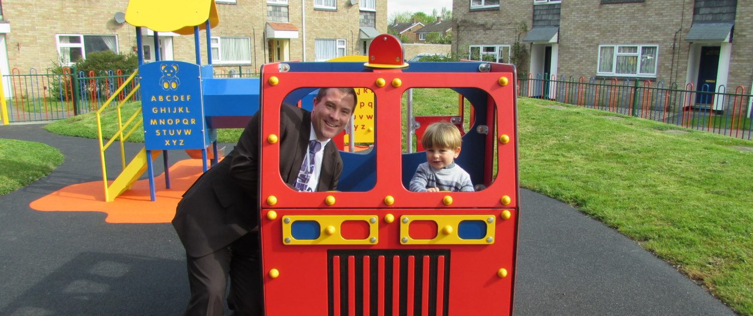 Man and son in the front seats of a child's fire engine in a playground surrounded by houses