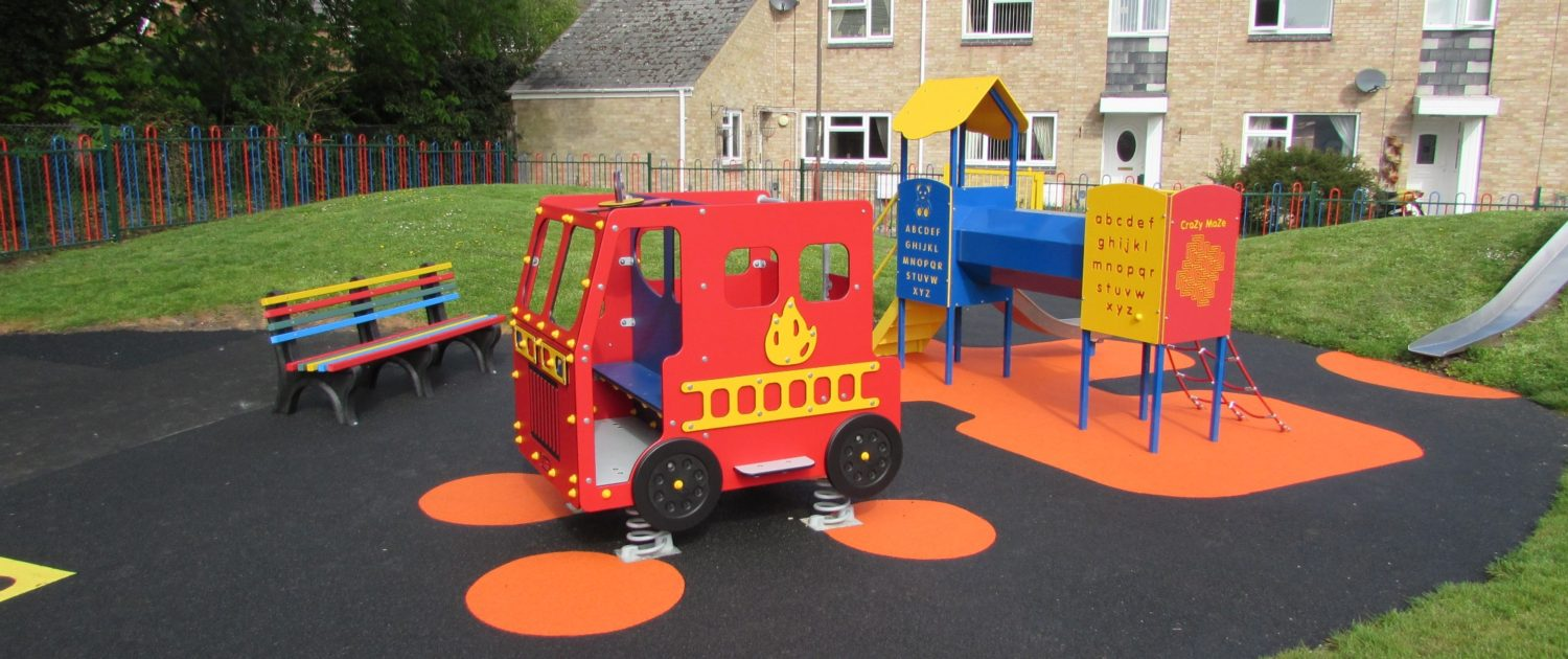 A childs playground with a fire engine, colourful wooden bench, slide and climbing tower