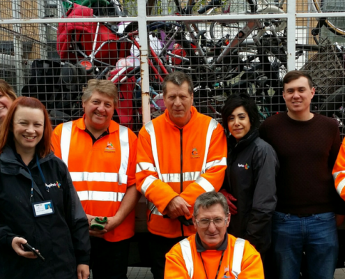 Staff from bpha standing in front of a waste truck full of bikes and other rubbish